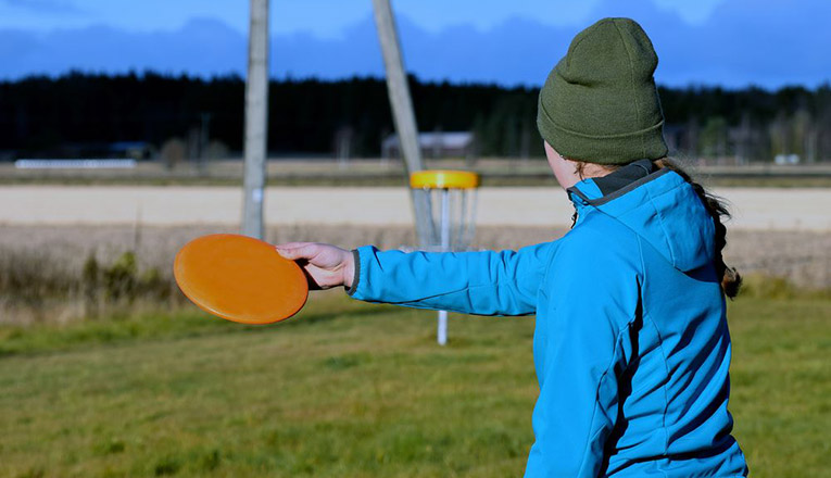 young woman aiming disc to target