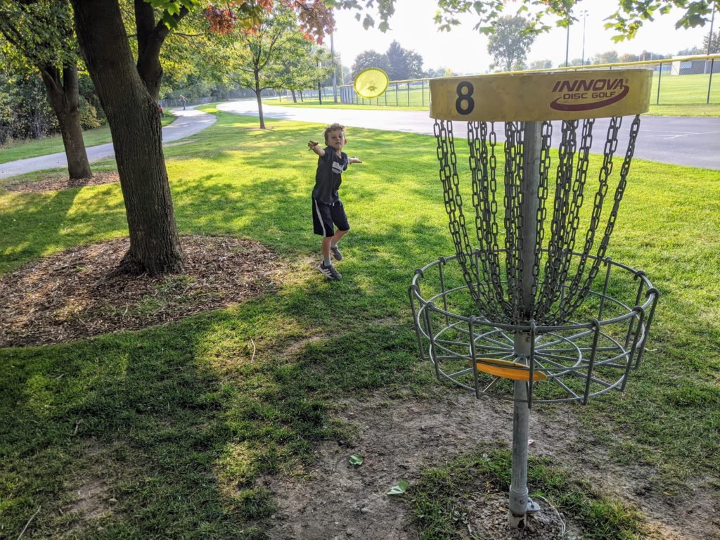 Kid putting in disc golf